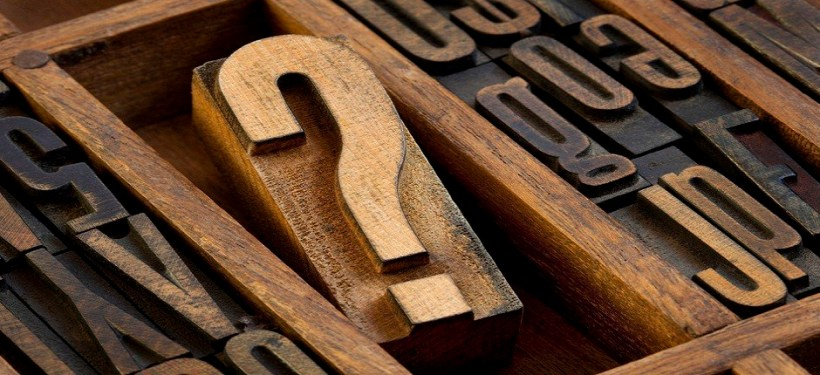 question mark - vintage wooden letterpress type block in old typesetter drawer among other letters stained by ink